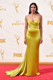 Padma Lakshmi was a stunning, statuesque beauty at the Emmys in a chartreuse satin strapless gown by Romona Keveza, featuring a ruched bodice, a long train, and a perfectly constructed silhouette that fit her like a glove.