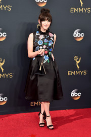 Maisie Williams tied her look together with a black velvet pyramid purse.