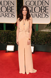 Kristen Wiig showed some skin in a deep-plunging nude dress at the Golden Globe Awards.