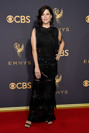 Neve Campbell complemented her dress with a black box clutch.