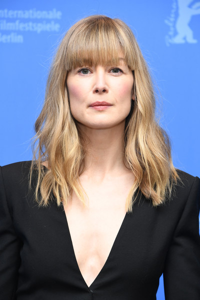 Rosamund Pike wore her hair in subtle waves with eye-grazing bangs at the Berlinale photocall for '7 Days in Entebbe.'
