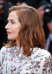Isabelle Huppert attended the Cannes Film Festival 70th anniversary event wearing her hair in a side-parted wavy style.