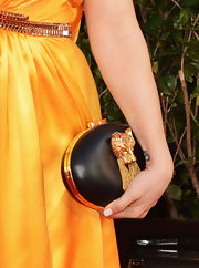Alyssa Milano's black leather clutch was embellished with what looks like a gold fox eating spaghetti.