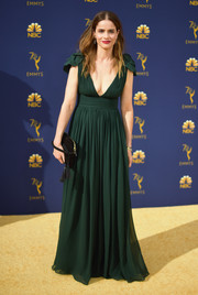 Amanda Peet attended the 2018 Emmys wearing a forest-green Michael Kors empire gown with a plunging neckline and cap sleeves.