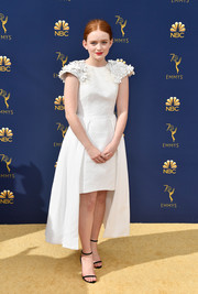 Sadie Sink was sweet and elegant at the 2018 Emmys in a white Hiraeth cocktail dress with floral-appliqued shoulders and a high-low hem.