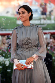 Golshifteh Farahani looked divine at the Venice International Film Festival closing ceremony with this flower-embellished silver clutch and gray dress combo.