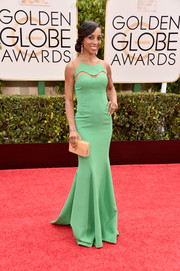 Shaun Robinson cut a vibrant figure on the Golden Globes red carpet in a bright green gown with peekaboo detailing along the yoke.