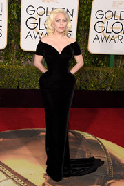 Lady Gaga wore a custom Atelier Versace off-the-shoulder velvet gown, featuring an exaggerated hourglass silhouette, to the Golden Globes.