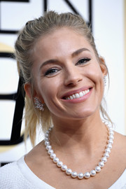 Sienna Miller went for classic styling with a pearl necklace.