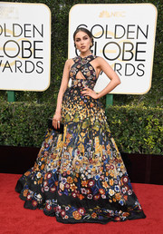 Olivia Culpo contrasted her colorful frock with a simple black snakeskin clutch.