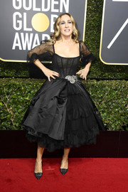 Sarah Jessica Parker attended the 2018 Golden Globes looking fancy in a black Dolce & Gabbana corset dress with net sleeves and a voluminous skirt.