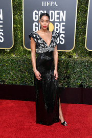 Laura Harrier hit the 2019 Golden Globes red carpet wearing a black Louis Vuitton column dress with a printed bodice and a sequined skirt.