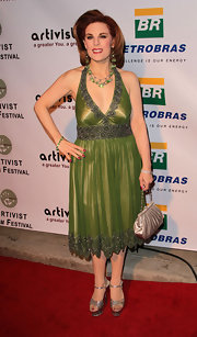 Katherine Kramer paired a beaded green evening dress with a champagne colored satin clutch.