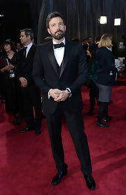 Ben Affleck dressed in style on his big night at the 2013 Oscars in a black satin peak lapel, one button three piece tuxedo.