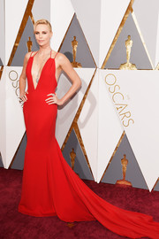 Charlize Theron looked ageless in a plunging red fishtail gown by Christian Dior at the Oscars.