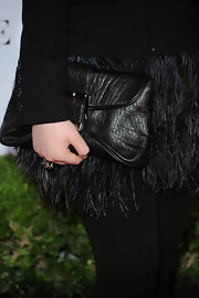 Jennette's subtle black leather clutch doesn't distract attention from her statement making feathered skirt.