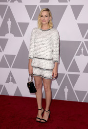 Margot Robbie attended the 2018 Academy Awards nominees luncheon looking stylish in a white Chanel mini dress with metallic detailing.