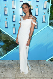Sasha Lane attended the Bombay Sapphire Artisan Series Finale wearing a white column dress with a draped neckline.