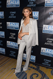 Zendaya Coleman shined in satin gray while wearing a button-down blazer over a cami and fitted pants