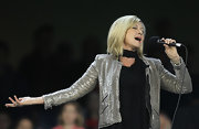 Olivia Newton-John performed at the AFL Rd 10 wearing a glittering jacket.
