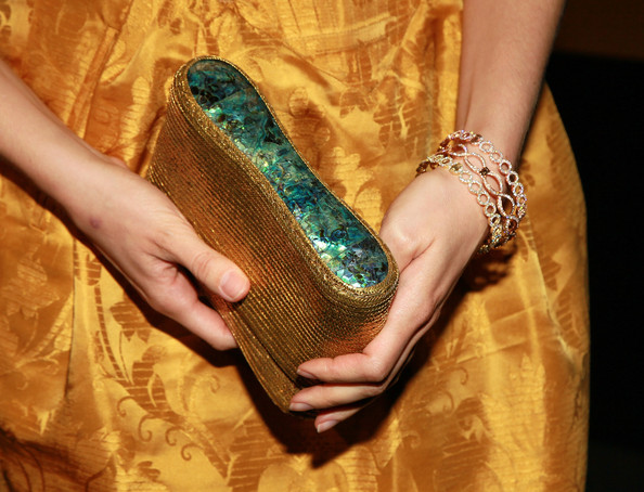Alison Brie attended the AMC Emmy Awards after-party carrying a glam mother-of-pearl-inlaid metallic gold clutch.