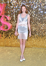 Lily Cole styled her dress with a perforated bronze box clutch.