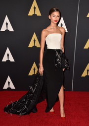 Zendaya Coleman went for dramatic elegance at the Governors Awards in a Christian Siriano strapless gown featuring a white bodice, a black side-slit skirt, and a flowing feather-embellished train.