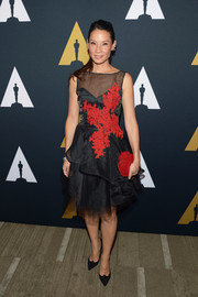 Lucy Liu rounded out her black and red-themed look with a flower-adorned suede clutch.