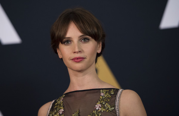 Felicity Jones styled her hair into a loose updo with parted bangs for the Governors Awards.