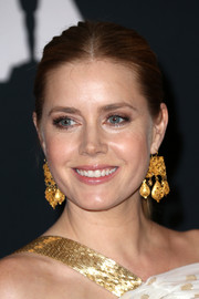 Amy Adams balanced out her minimalist 'do with ultra-glam gold chandelier earrings.