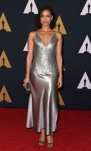 Gugu Mbatha-Raw looked ultra sophisticated at the Governors Awards in a silver Narciso Rodriguez slip dress with a plunging neckline and a textured bodice.