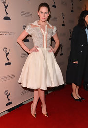 Christa B. Allen showed off her feminine figure in a classic A-line dress with a full skirt and silver embellishments.
