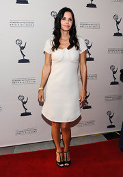 Courteney Cox was out in Hollywood last night for the Academy of Television Arts & Sciences 'Cougar Town' event. The actress opted to wear a white Marc Jacobs sheath dress with thick piping at the bust. She took a minimalist approach to her red carpet look with black heels and effortless curls.