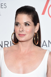 Debra Messing teamed her hairstyle with massive gold hoops.