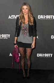 Amber Lancaster donned ladylike black pumps over lace floral tights. A leather jacket and loose graphic tee finish the look.