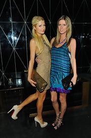 Paris Hilton accented her flapper-inspired look with an oversize  bronze foil clutch.
