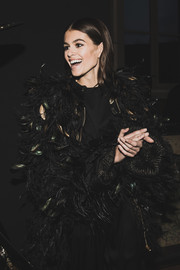 Kaia Gerber got dolled up in a chic black feather coat for the Alberta Ferretti fashion show.