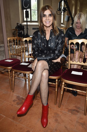 Carine Roitfeld amped up the edge factor with red ankle boots teamed with a grommeted leather outfit at the Alberta Ferretti fashion show.