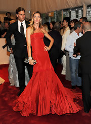 Gisele Bundchen teamed her radiant Alexander McQueen gown with the late designer's black and gold lace knuckle duster clutch.