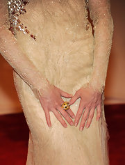 Renee Zellweger paired her shimmering frock with a gold cocktail that was encrusted with gemstones.