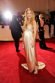 Kate Hudson showed off her growing baby bump in a satin champagne strapless gown. Gemstone detailing embellished the bodice of her dress. A half up hairstyle completed her golden look.