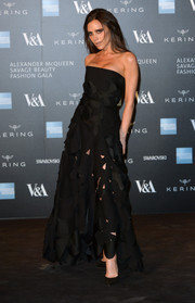 Victoria Beckham was edgy-elegant at the Alexander McQueen: Savage Beauty exhibition in a strapless black cutout gown from her own line.