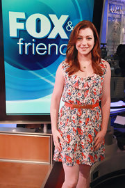 Alyson Hannigan wore an orange floral print cocktail dress with a neck ruffle. She completed the look with a vibrant belt to cinch her waist.