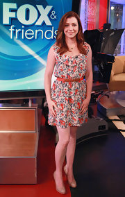 Alyson Hannigan visited the set of 'Fox & Friends' in a feminine floral print dress and classic nude patent pumps.