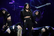 Demi Lovato teamed a cropped denim jacket by RtA with a crop-top and matching pants for a performance.