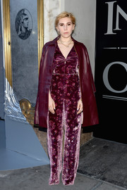 Zosia Mamet attended the American Express Platinum Card celebration wearing a burgundy floral velvet jumpsuit by Rebecca Taylor.