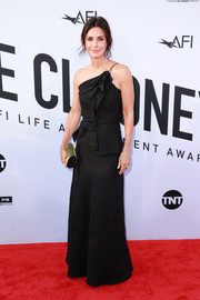 Courteney Cox styled her dress with a studded clutch.