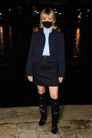 Maisie Williams styled her look with a pair of black knee-high boots.