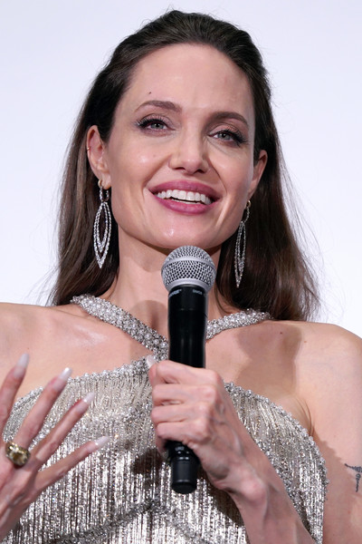 Angelina Jolie Half Up Half Down [maleficent: mistress of evil,microphone,singer,singing,audio equipment,music artist,performance,technology,event,nail,talent show,angelina jolie,stage,japan,tokyo,premiere]