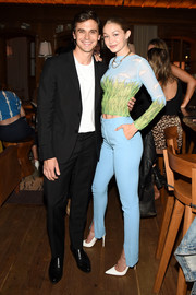 Gigi Hadid coordinated her top with a pair of blue front-split trousers by Victoria Beckham.